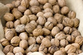 Background image of a basket full of a raw walnuts.