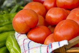 Closeup image of a group of big red tomatoes in a wooden basket.