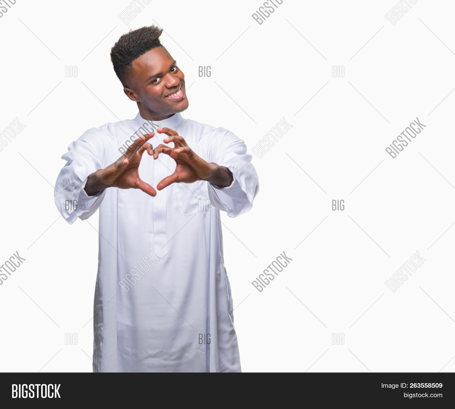 8bc5dc1fd3c032 Young arabic african man wearing traditional djellaba over isolated  background smiling in love showing heart symbol