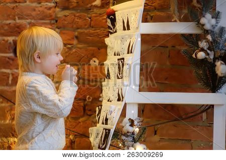 Happy Little Boy Takes Sweet From Advent Calendar On Christmas Eve. Traditional Christmas Calendar F