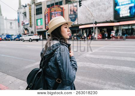 A Female Traveler Waiting To Cross The Road