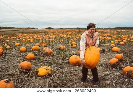 Adult Woman (30s) Attempts And Struggles To Lift And To Pick Up A Giant Pumpkin From A Pumpkin Patch