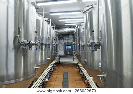 Modern Automated Beer Factory. Lines Of Metal Tanks In Modern Brewery. Shopfloor With Brewery Facili