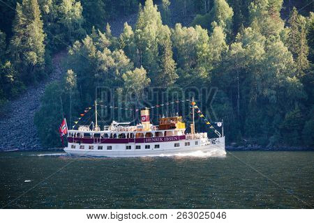 DALEN, NORWAY - JULY 16, 2018: M/S Henrik Ibsen ferry boat crosses the Bandak lake, part of the Telemark Canal route, during a popular historical boat trip through spectacular Norwegian nature