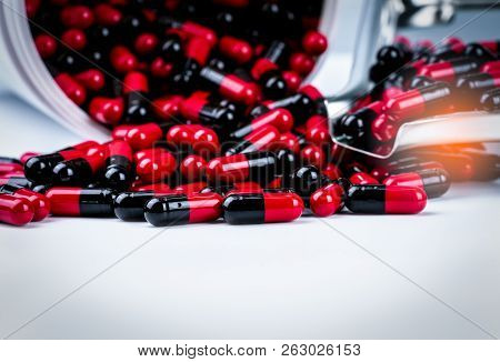 Red-black Antibiotic Capsule Pills Spill Out Of White Plastic Bottle Container And Drug Tray. Pharma