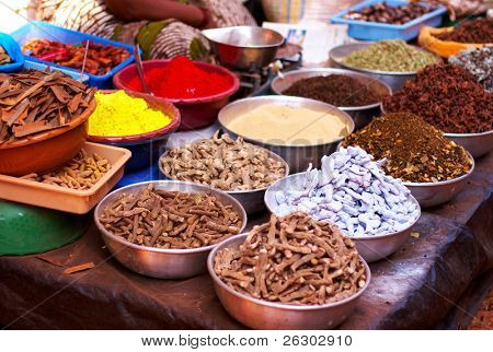 Different spices and herbs in metal bowls on a street market in India