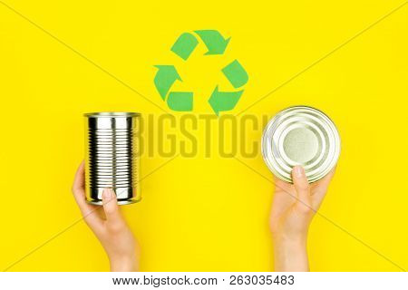 Human Hands With Metal Aluminium Can Jar On Yellow Background With Green Recycle Reuse Arrow Sign Sy