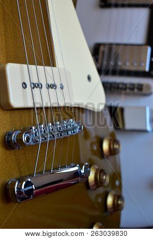 White And Gold Top Electric Guitars Details. Body Closeup: Strings, Bridge, P90 And Humbucker Pickup