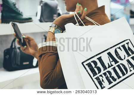 Black Friday. Close Up Of A Cropped View Of A Young Woman Holding Paper Shopping Bags While Is Looki