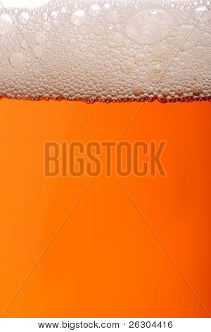 A pint of beer with lots of frothy bubbles