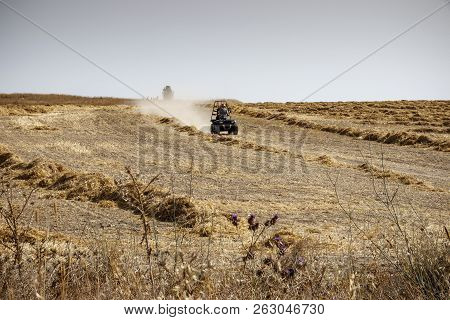 A Man On An All-terrain Vehicle Rides Across The Field With Collected Wheat, Leaving Behind Him Clou
