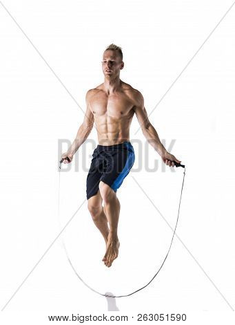 Shirtless Muscular Man Jumping Rope In Studio