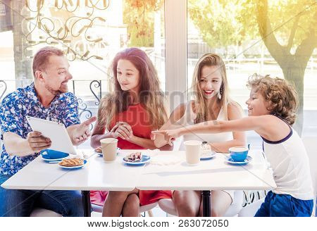 Happy Family Eating Breakfast And Using Tablet. A Big Company With A Digital Tablet In Cafe, Smiling