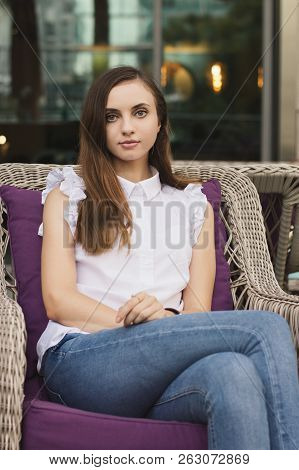 Beautiful European Female Sitting Outside In A Purple Armchair, Casual Style