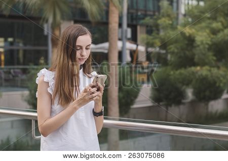 Young European Female With Brown Hair And In White Smart Casual Blouse Standing Outside At Business