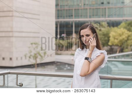 Young European Business Woman Standing In Business District And Speaking Via Mobile Phone With Aston