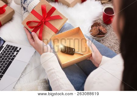 Christmas Present. Woman Opening Christmas Dream Gift With Car Key Inside