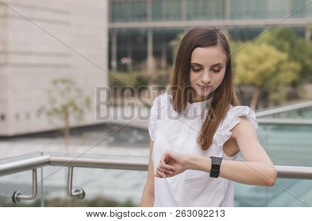 Young European Female Standing In City Business District And Looking At Her Hand Watches. Time Manag