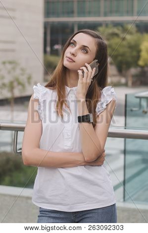 Young European Female Standing In The Business District And Talking Via A Mobile Phone. Mobile Phone