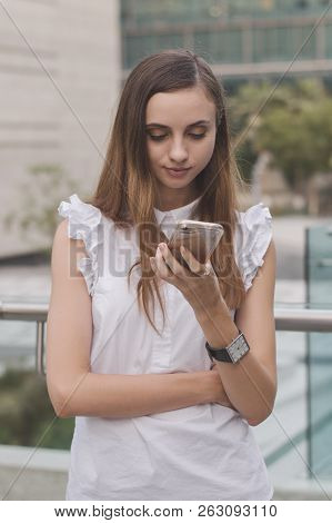 Young European Woman Holding A Mobile Phone And Looking At Its Screen. Female Entrepreneur Checking