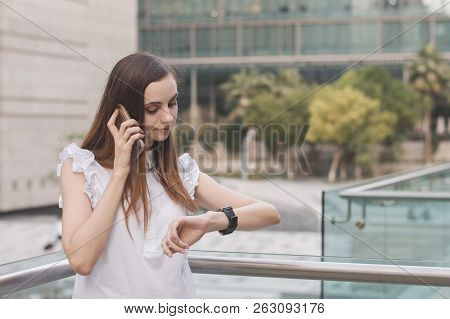 Busy Business Woman Talking Via A Mobile Phone And Looking At Watches On Her Wrist. Time Management