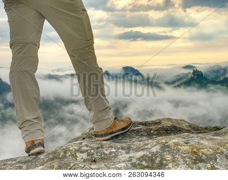 Hiker Legs In Light Outdoor Trousers And Comfortable Leather  Trekking Boots On Rocky Peak. Misty Va