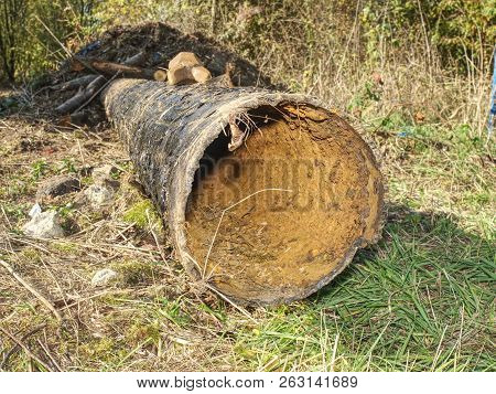 Long metal pipe laying on ground. Broken rusty steel tube. Open trench with water pipe and heap of ground near. poster
