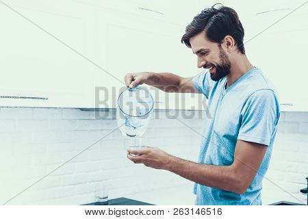 Man In Shirt Drinking Water In Kitchen At Home. Healthcare Concept. Fresh Water. Man In T-shirt. Ma