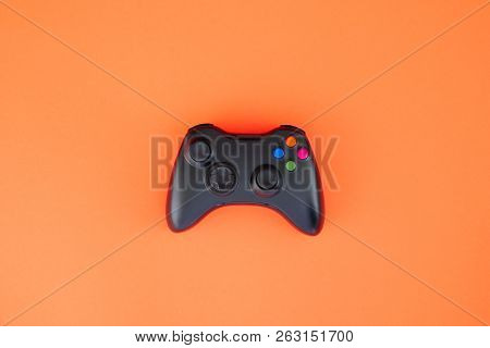 Black gamepad, controller on a red background. Computer game competition. Gaming concept. Wireless control of the game. poster