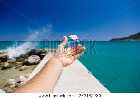 Hairy Male Arm And Hand With Glass Ball, Next To The Greek Sea. Jetty Lead Us Deep In The Water. Spl