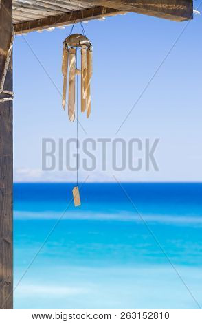 Wind Chimes Made Of Bamboo, With Beautiful Turquoise And Azure Blue Sea And Sky.