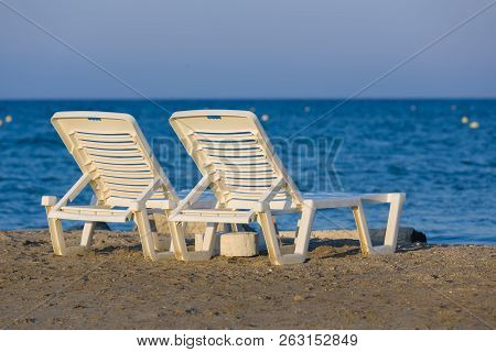 White, Plastic Sunbeds At Golden Hour On Sandy Beach Of Zakynthos, Greece