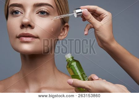 Young Woman Looking Calm While Using Facial Serum