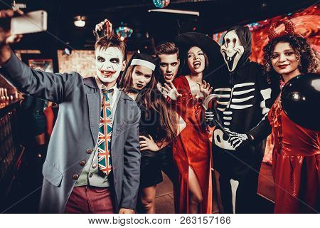 Young People In Halloween Costumes Taking Selfie. Young Smiling Man Taking Selfie Together With Grou