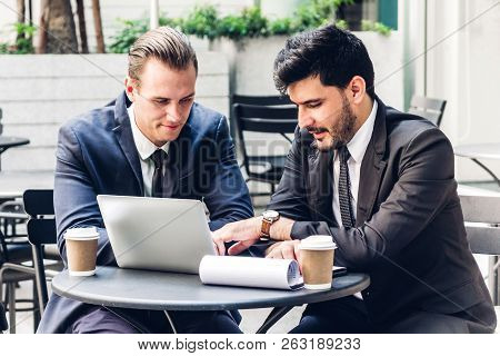 Image Of Two Businessman Coworkers In Black Suit Talking And Working With Laptop Computer And Discus