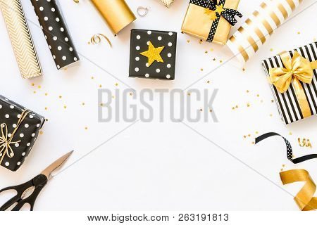 Top View Of Gift Boxes And Wrapping Materials In Various Black, White And Golden Designs. Flat Lay,