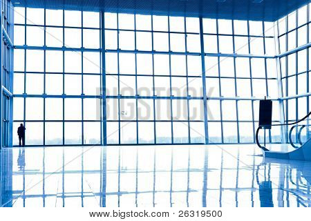 Person silhouette in glass corner of office centre