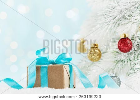 Christmas Gift Or Present Box And Fir Tree With Balls Decorations Against Turquoise Bokeh Background