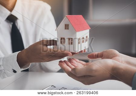 Real Estate Agent Congratulations To New Buyer By Giving House Model To Client In The Agency Office.