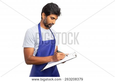 Store Manager Or Indian Owner Writing On Paper Checklist Clipboard With Focused Look Isolated On Whi