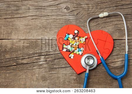 Heart Puzzle Red And Color Pills And Stethoscope On A Wooden Background Background. Concept Treatmen