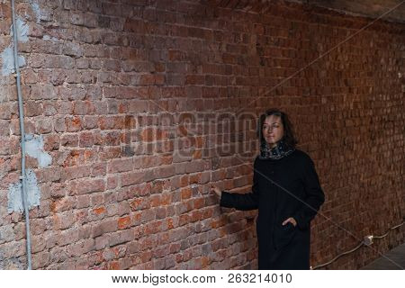 The Young Lady Deep In Thought In Black Stylish Coat With Black Scarf Walking In The Industrial Tunn