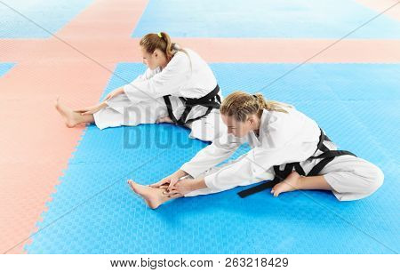 Two Girl Wearing In White Kimono And Black Belts, Training Their Flexibility Before Training In Figh