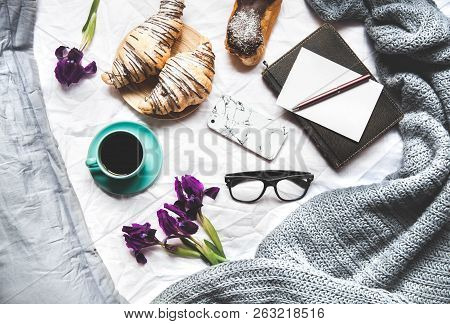 Breakfast In Bed. Morning, Croissant, Coffee, Flowers And A Notebook With A Pen. Planning A
