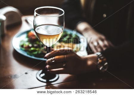 Female Hand With Glass Of Wine And Food In The Background A