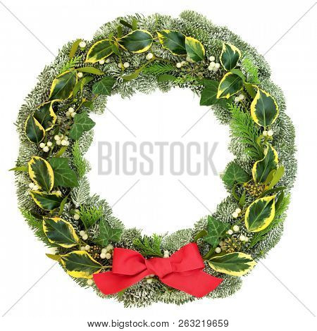 Traditional winter and Christmas natural wreath with snow covered spruce pine fir, mistletoe, cedar and ivy leaves with red bow isolated on white background.