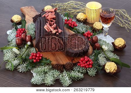 Yule chocolate decorated log cake for the christmas season with winter flora, alcoholic drink and foil wrapped chocolates on rustic oak wood background.