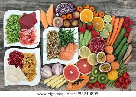 Diet health food concept with a large variety of vegetables, fruit, meat, fish, grain salad and spice with foods high in  protein, antioxidants, dietary fibre, anthocaynins and vitamins. Top view.