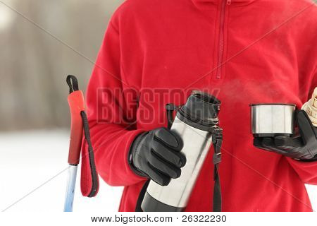 Cross-country skier pouring hot drink from thermos to a cup