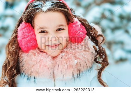 Winter Portrait Of Happy Kid Girl In Pink Earmuffs Walking Outdoor In Snowy Winter Forest. Happy Chi